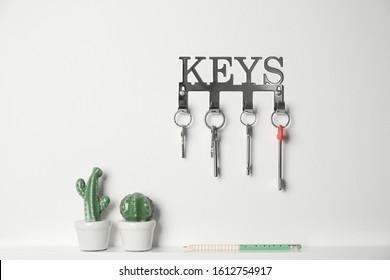 Metal key holder on light wall indoors