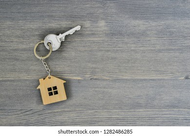 Metal key lock home in bamboo keychain for wooden rustic gray background. Real estate purchase offer concept. Copy space.