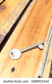 Metal Key on Wooden Table in the Sun