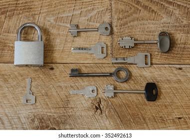 a lot of metal keys and a steel lock on a wooden boards / Many keys one lock