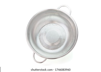 Metal kitchen utensils, Stainless steel colander on a white background. Top view