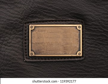 metal label on old black leather background