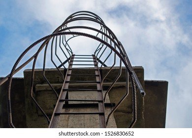 A metal ladder running vertically from the bottom up over a concrete angular structure with rounded ribbed safety iron holders along the entire length of the ladder against a blue cloudy sky