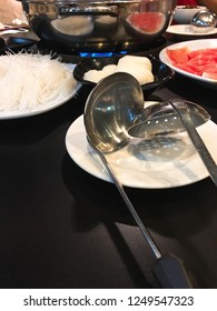 A metal ladle and a strainer ladle, commonly used in Chinese hot pot, on a white plate. A plate of rice noodle, radish slices and sliced raw meat and a metal hot pot can be seen in the background.