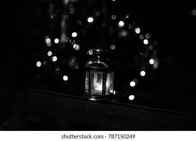 Metal lamp with candle at night with bokeh. Black and white photo