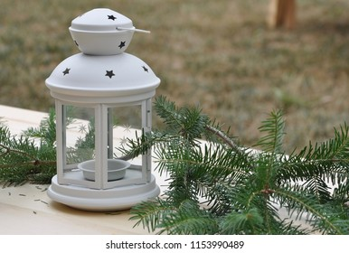 Metal lamp with pine tree branches in wooden table