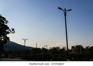 Metal lamp post against blue sky background