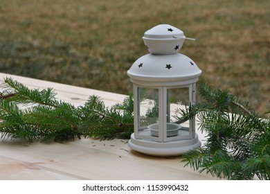 Metal lantern with pine tree branches in wooden table