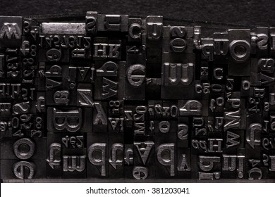 Metal Letterpress Types. A background from many historic typographical letters in black and white with black background.