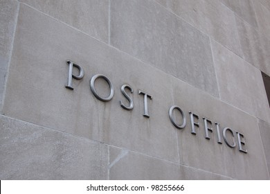 Metal letters that spell post office fastened to the side of a building.