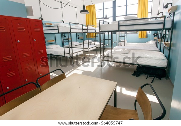 Metal locker, table and double-decker beds inside hostel room with tall windows.