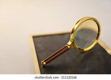 Metal magnifying glass standing on  wooden black board with beam of light.