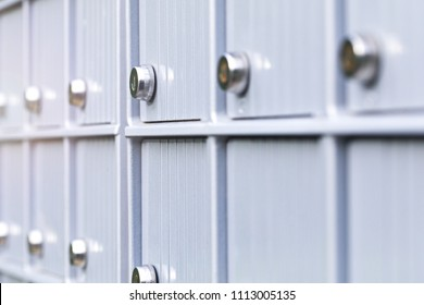 Metal mailboxes and lock in business center of an urban neighborhood. Mail boxes in rows at entrance of modern building. Security storage mailroom for secret files or corporate postal service.