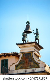Metal male figures. Front view of the bell with two men holding hammers. Astronomical clock tower (Torre dell'Orologio) with statues Macc de le Ure in Piazza Loggia, Brescia, Lombardy, Italy, 1546.