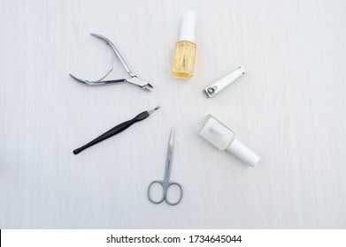 Metal manicure accessories and care products for nail and cuticle. Cuticle clippers, small cuticle scissors, nail clippers, cosmetic oil to soften the cuticle and a transparent firming nail Polish.