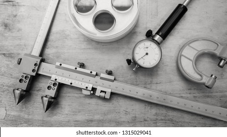 Metal measuring instruments on a wooden table. Product quality control. Black and white.