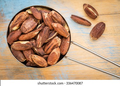 metal measuring scoop of roasted pili nuts against wood background