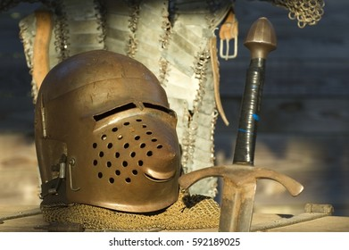 Metal medieval armor and sword on wooden chest