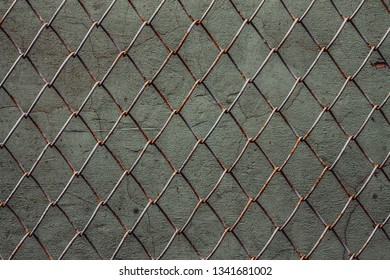 metal mesh chain-link, texture on the background of a concrete wall for various creative tasks of building designers
