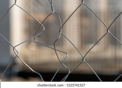 Metal mesh fence close-up. Abstract and Blurred focus. Construction site is not of focus behind the iron fence. For background and street art decoration.