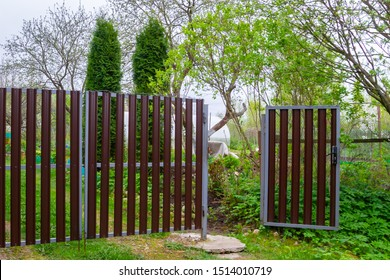 Metal mesh fence with open door in garden in spring