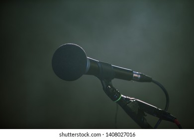 Metal microphone in holder on dark background. Close-up