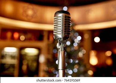metal microphone on a background of a blurred Christmas tree