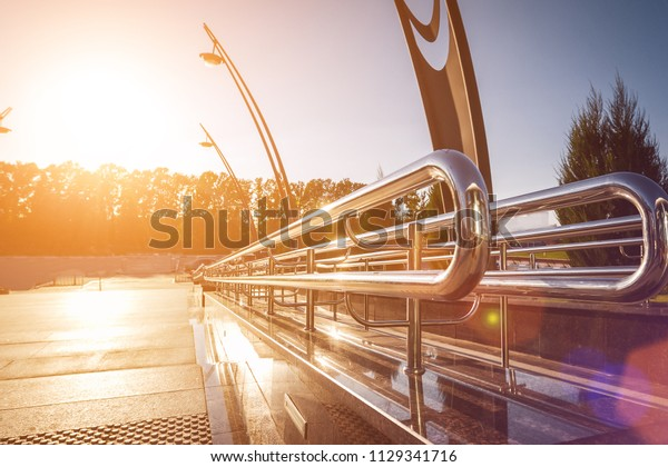 metal modern clean glossy handrails of the road outdoors. construction illuminated by sun light of the sunset surrounded by the trees and futuristic lamps