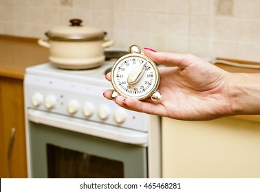 metal modern kitchen timer on the background of the kitchen, stove and pans, Closeup of female hands. Housewife or chef using timer eggtimer, round alarm clock,