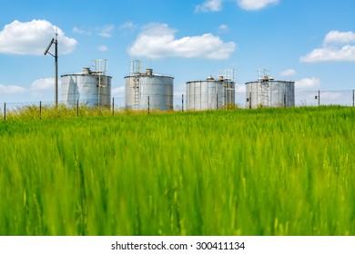 Metal modern silos on the large green field