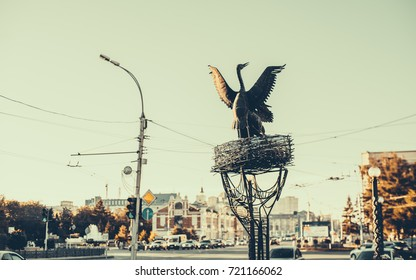 Metal monument of flapping crane or heron near its nest located in the centre of Novosibirsk in Russia in front of museum of local lore, road and cars in background, vintage color, autumn sunny day