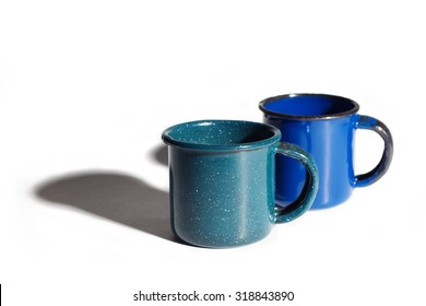 Metal mugs on white background with a long shadow.