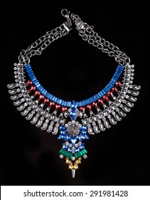 metal necklace with red and blue stones