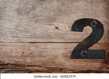 Metal Number 2 Nailed to Weathered Wood Post
