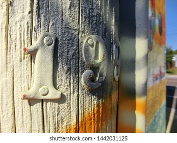 Metal numbers nailed to telephone pole with vibrant spray paint color
