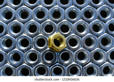 A lot of metal nuts and one gold. Abstract industry background. Natural photo.
