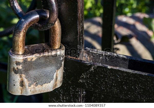 Metal padlock on fence close-up
