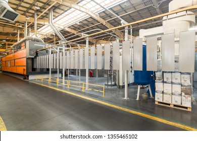 Metal panels are suspended on an overhead conveyor line. Painting products in an electrostatic field.