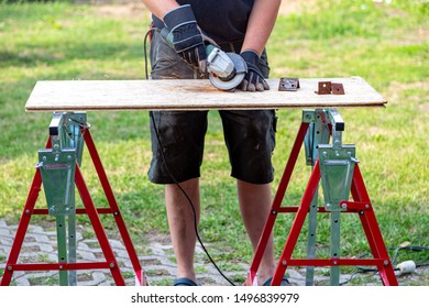 Metal parts are ground on workbench, industrial background