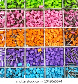 Metal parts with multi-colored plastic tips, arranged in cells