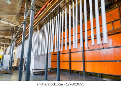 Metal parts are suspended on an overhead conveyor. Line painting in an electrostatic field.