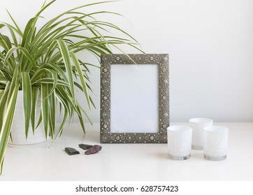 metal photo frame mock-up with candle holders and green plant