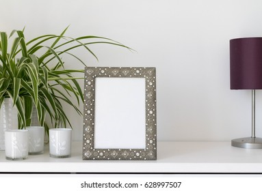 metal photo frame mock-up with plant and candle holders