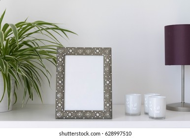 metal photo frame mock-up with plant, candle holders and desk lamp