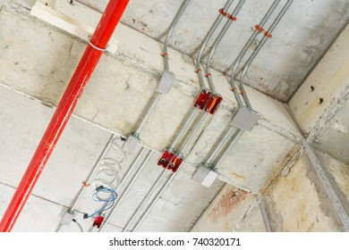 Metal pipes in Construction and fire sprinkler on red pipe are hanging from ceiling interior