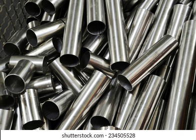 Metal pipes in a warehouse. Stack of new and shiny steel pipe in factory. Close Up