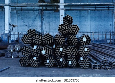 Metal pipes in a warehouse. Stacks of new round steel pipe in factory. Toned in cold tone