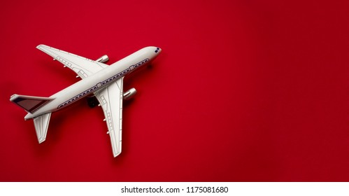 metal and plastic toy - airplane stand on red paper background. modern passenger plane isolated on red paper backdrop. travel and transportation idea.