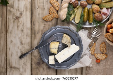 metal plate with baked potatoes and cucumbers and greens, rusks and cheese on a wooden table