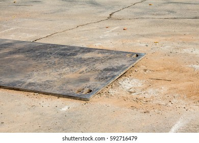 Metal plate covering a hole in the road for utility repair
